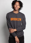 MEN WEARS GREY SWEATSHIRT WITH ORANGE BROOKLYN TEXT FLAT ACROSS THE CHEST, WITH ONE ARM CROSSED HIS BODY
