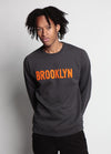 MEN WEARS GREY SWEATSHIRT WITH ORANGE BROOKLYN TEXT FLAT ACROSS THE CHEST WITH ARMS BEHIND HIS BACK