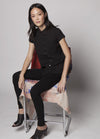 MODEL IN STUDIO IN BLACK MEAGAN PETER PAN TOP  SITTING IN CHAIR SIDE VIEW