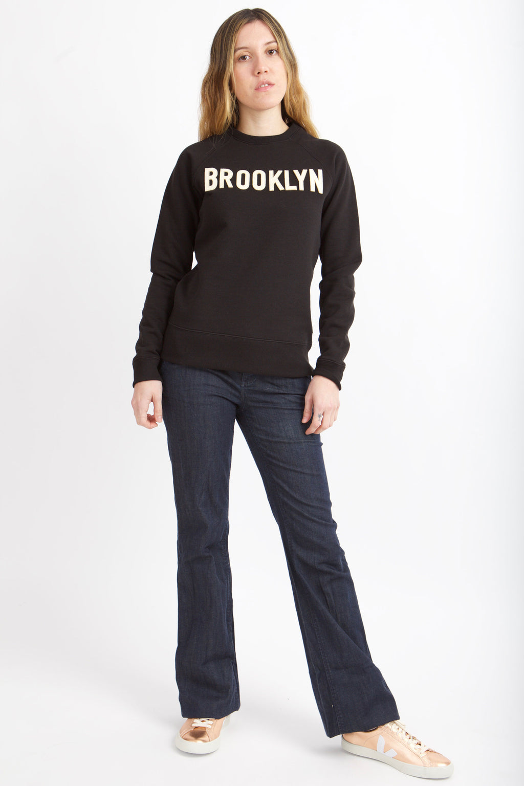 Woman standing wearing black sweatshirt with white letters spelling Brooklyn.