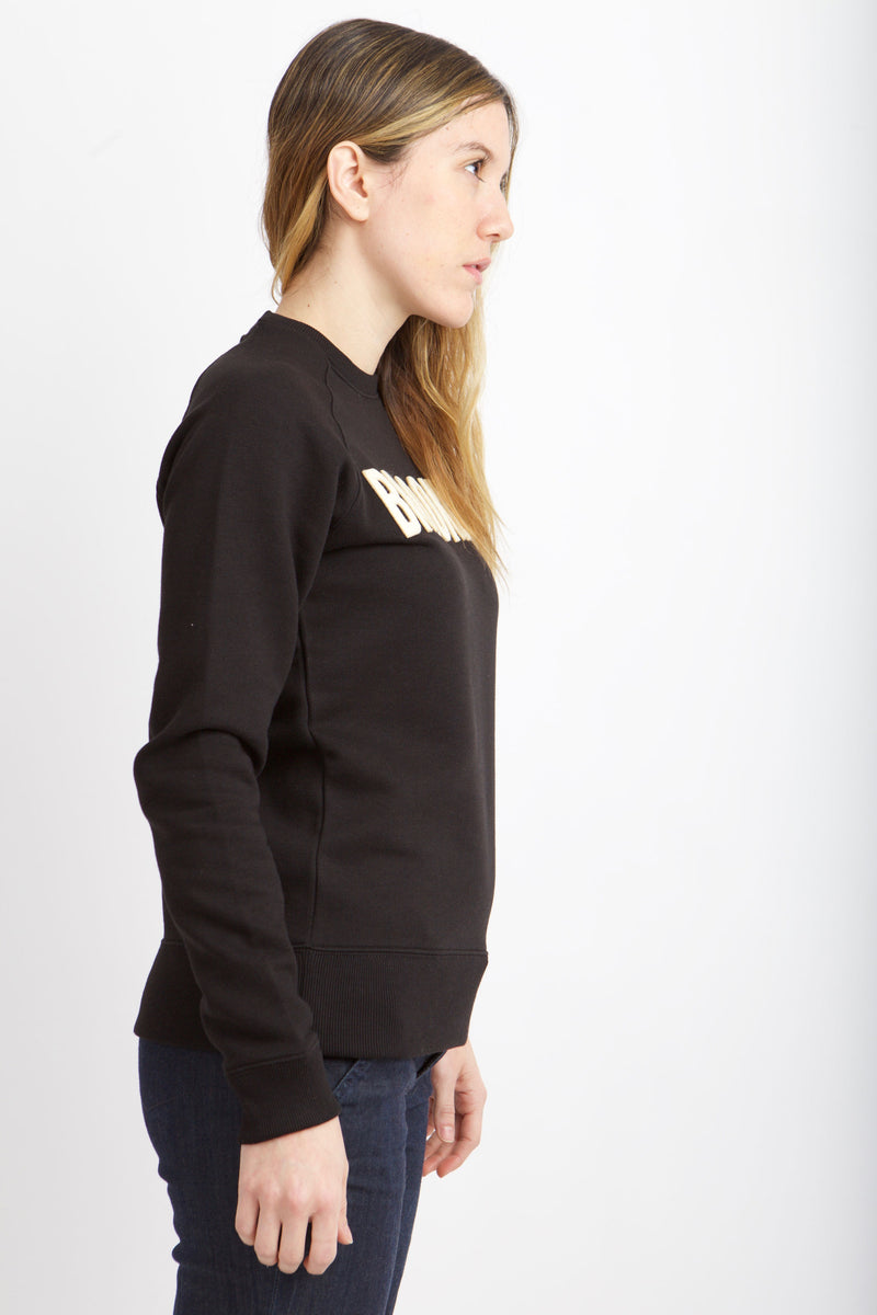 Side view of woman wearing black sweatshirt with white letters.
