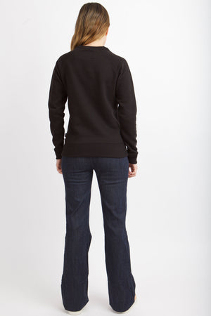 Back view of woman wearing black sweatshirt.