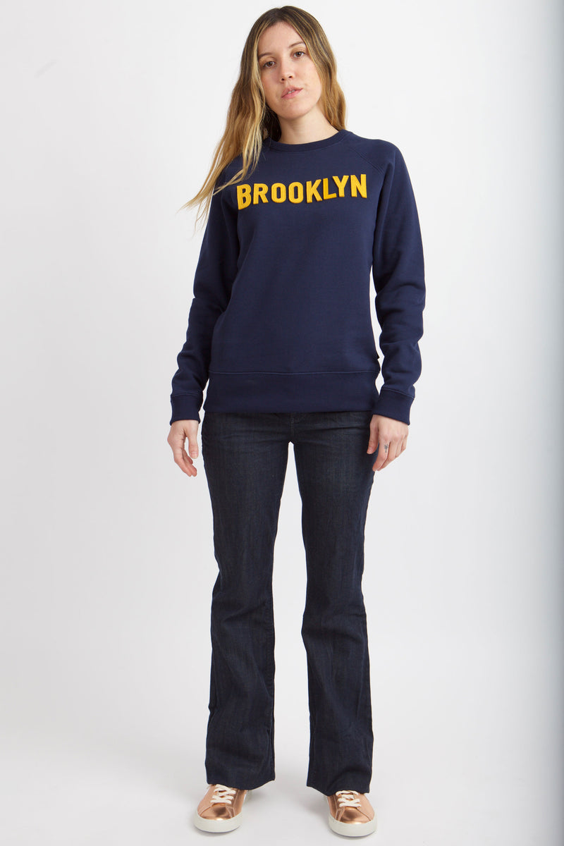 Woman wearing navy blue sweatshirt with yellow felt applique spelling Brooklyn