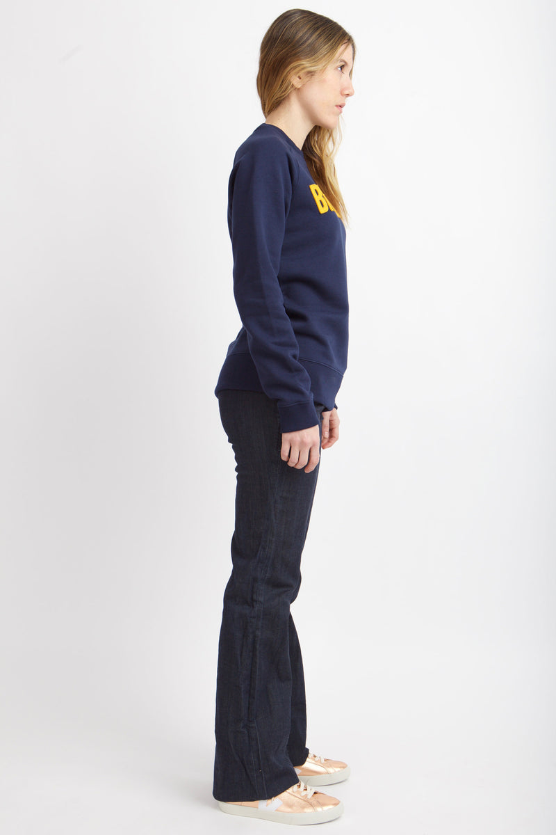 Side view of woman wearing navy sweathshirt.