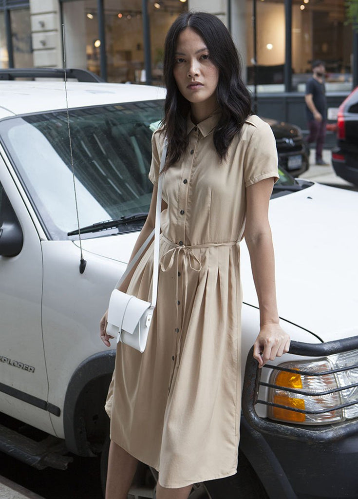 WOMEN LEANS ON CAR IN KHAKI DRESS WITH BUTTONS AND DRAW STRING WAIST
