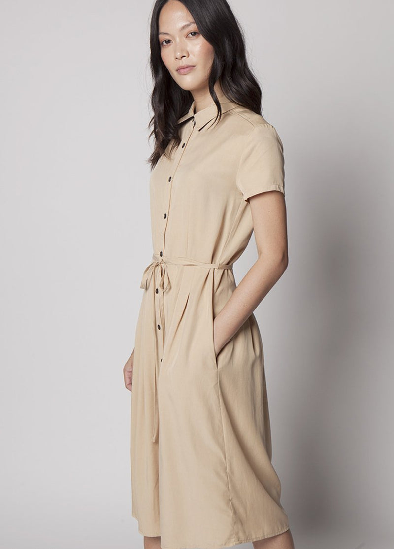MODEL WEARS KHAKI DRESS WITH BUTTONS AND DRAW STRING WAIST  WITH HAND IN POCKET