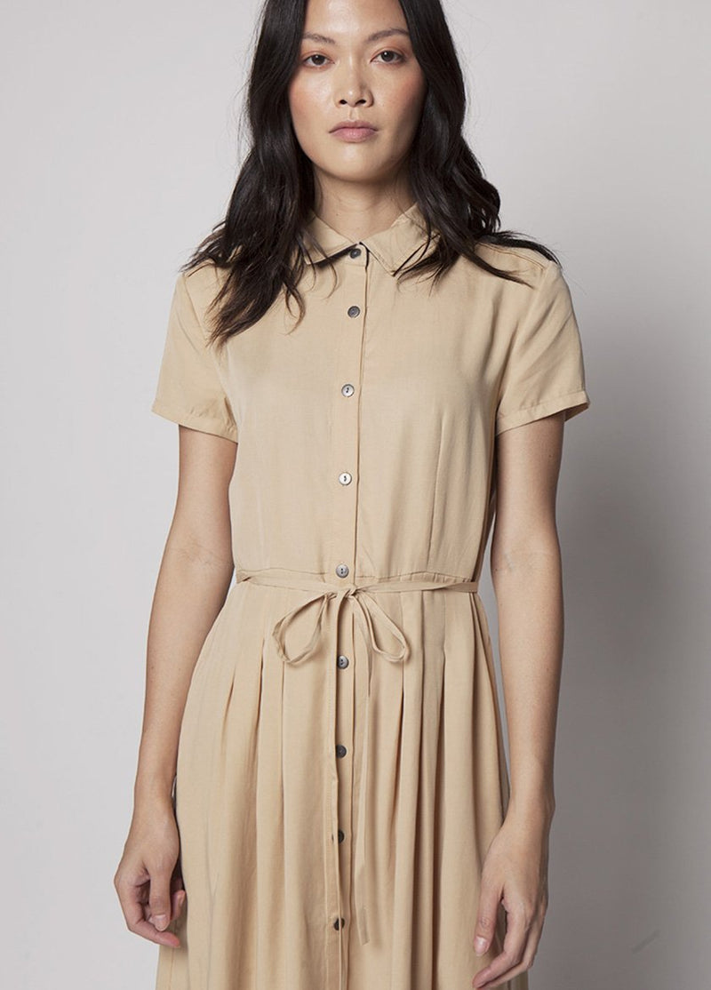 MODEL LOOKS AT CAMERA IN KHAKI DRESS WITH BUTTONS AND DRAW STRING WAIST