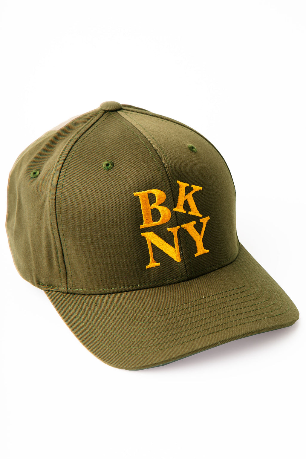 Baseball cap in olive with gold embroidered lettering BKNY.  The K of the letters is tilted slightly to the right.