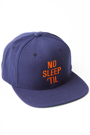 "Navy baseball cap with orange text embroidery on front bill saying ""No Sleep 'Till."""