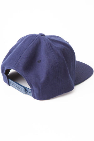 Back of baseball cap in navy showing adjustable plastic snaps.