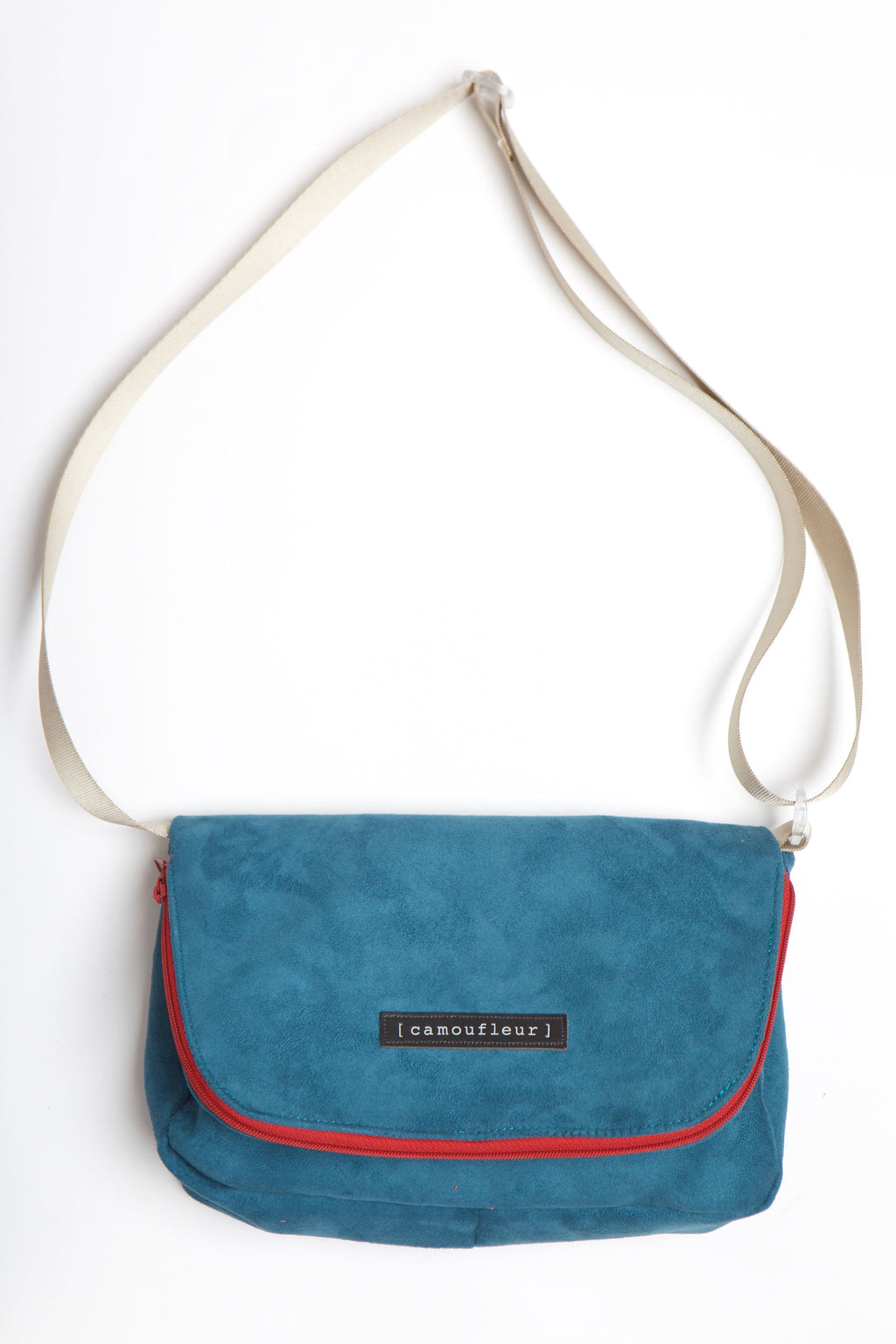 Teal cross over handbag with red zipper and tan colored strap.