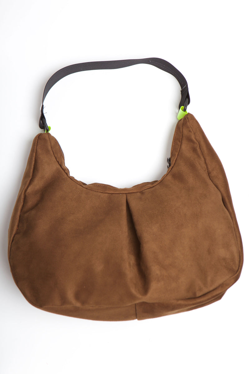 Brown suede vegan bag with black nylon strap and green neon plastic attachment.