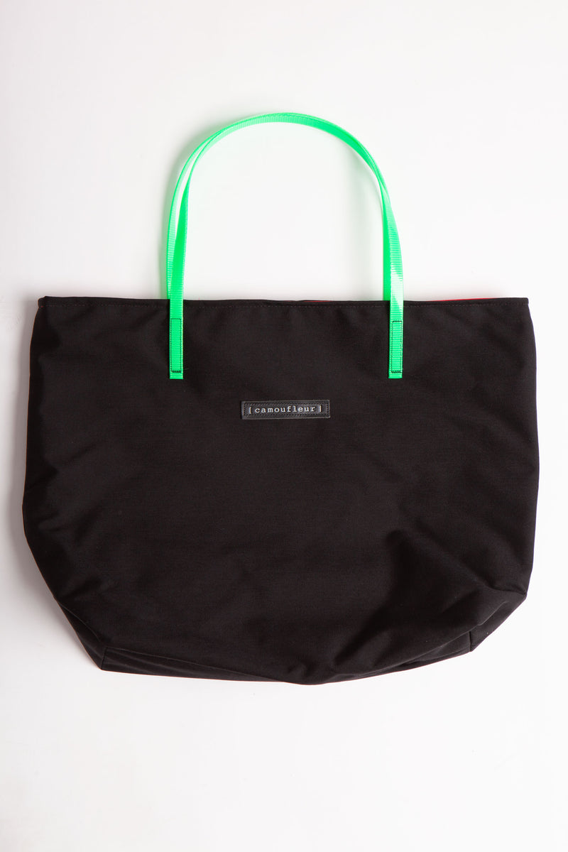Black Camoufleur bag is a horizontal rectangle with lime green plastic straps.  Bag lies flat on white surface.