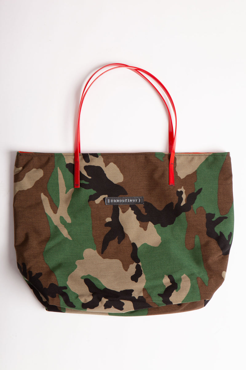 No 8 Tote lays horizontal on a flat surface.  The bag is a horizontal rectangle in woodland camo with a red plastic strap in the middle and the Camoufleur label in leather in the middle of the bag.
