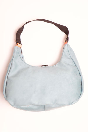 Ice blue vegan viola cross body bag with black handle and orange plastic attachment.