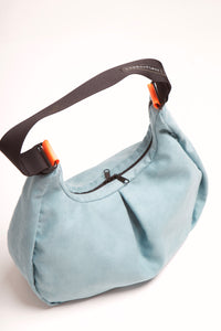 Overhead view of Viola cross shoulder bag with front fold and orange neon connector.