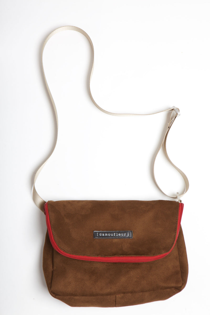 Brown suede fold crossbody bag with red zipper.