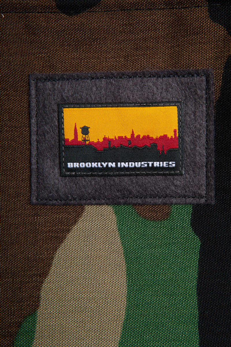 "DETAIL OF THE BROOKLYN INDUSTRIES PATCH ON THE FRONT OF THE 13"" LAPTOP BAG IN WOODLAND CAMO"