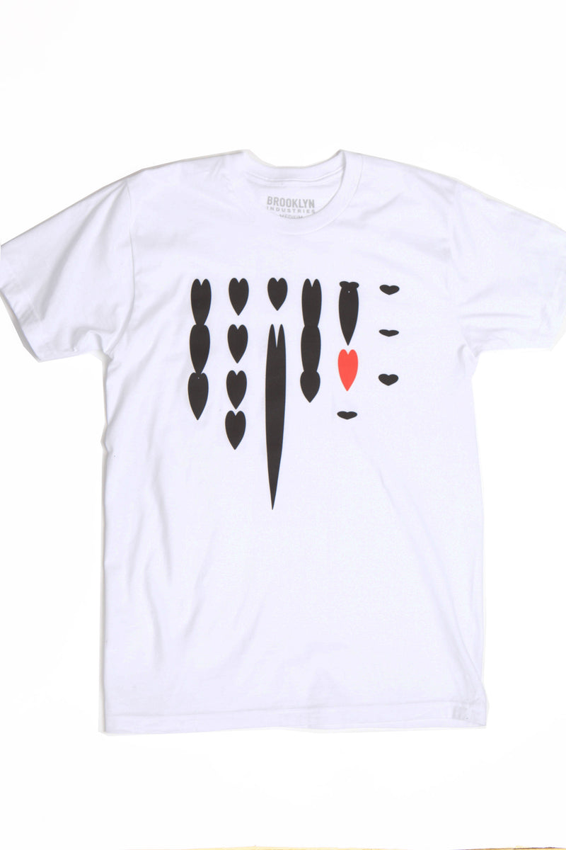 WHITE T-SHIRT LAYING FLAT WITH BLACK HEART CASCADING DOWN AND ONE RED HEART ON THE RIGHT.