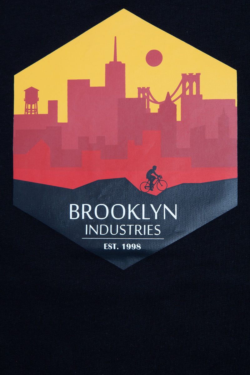 Hexagon graphic in various hues of burgundy and yellow with a silhouette of a man riding a bicycle and the words Brooklyn Industries below.