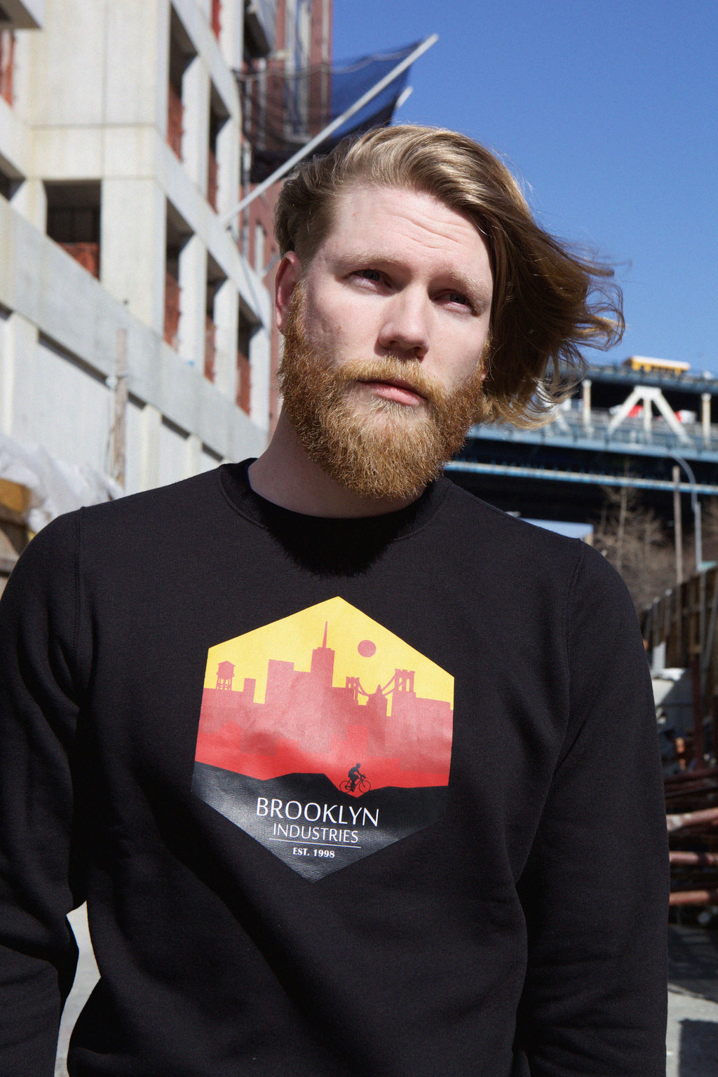 Portrait of man wearing black sweatshirt with bridge in background.  Hexagon print of skyline with words Brooklyn Industries below.