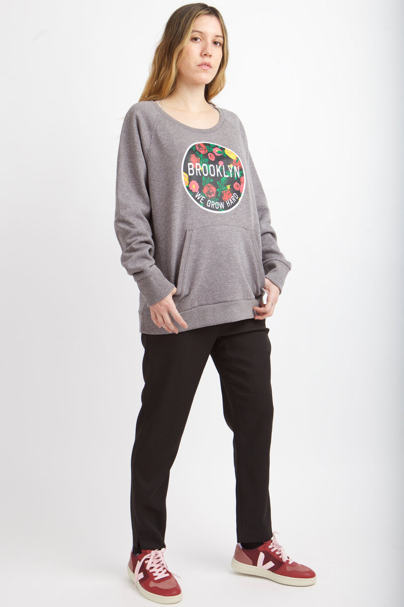 Full body image of woman in sweatshirt with black pants.