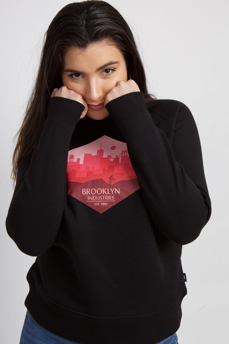 WOMEN IN BLACK SWEATSHIRT WITH FISTS UP TO FACE.  HEXAGON GRAPHIC OF CITY.