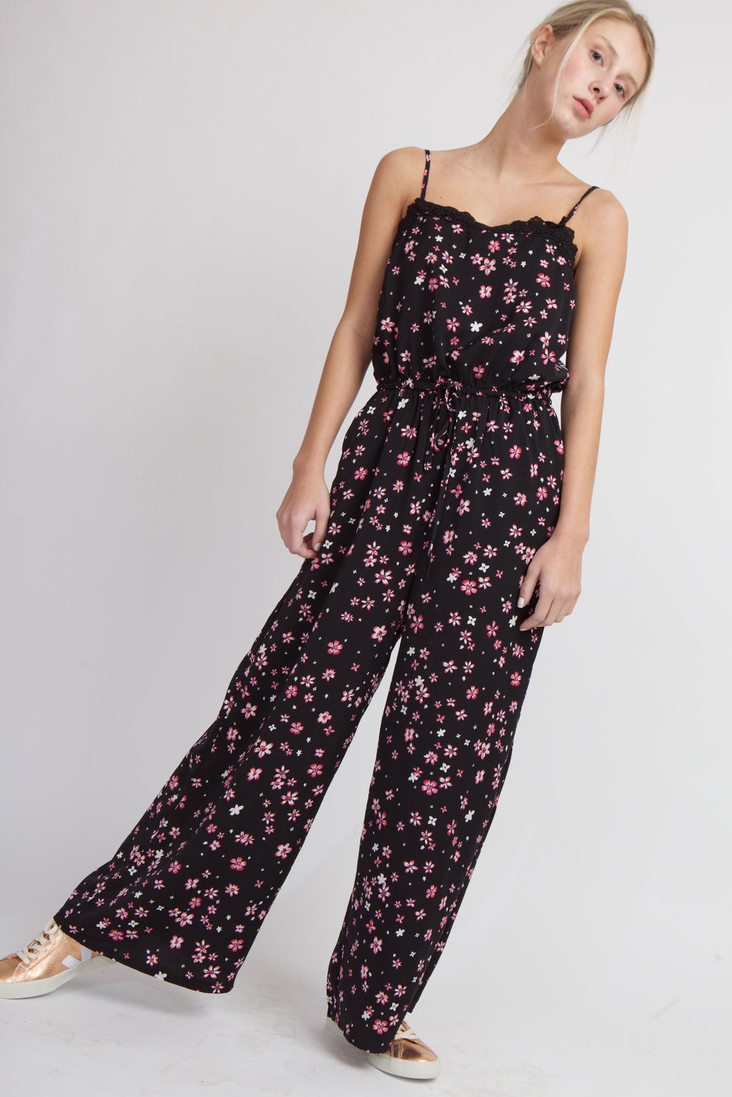 woman on one foot with black jumpsuit with pink ditsy florals and metallic sneakers