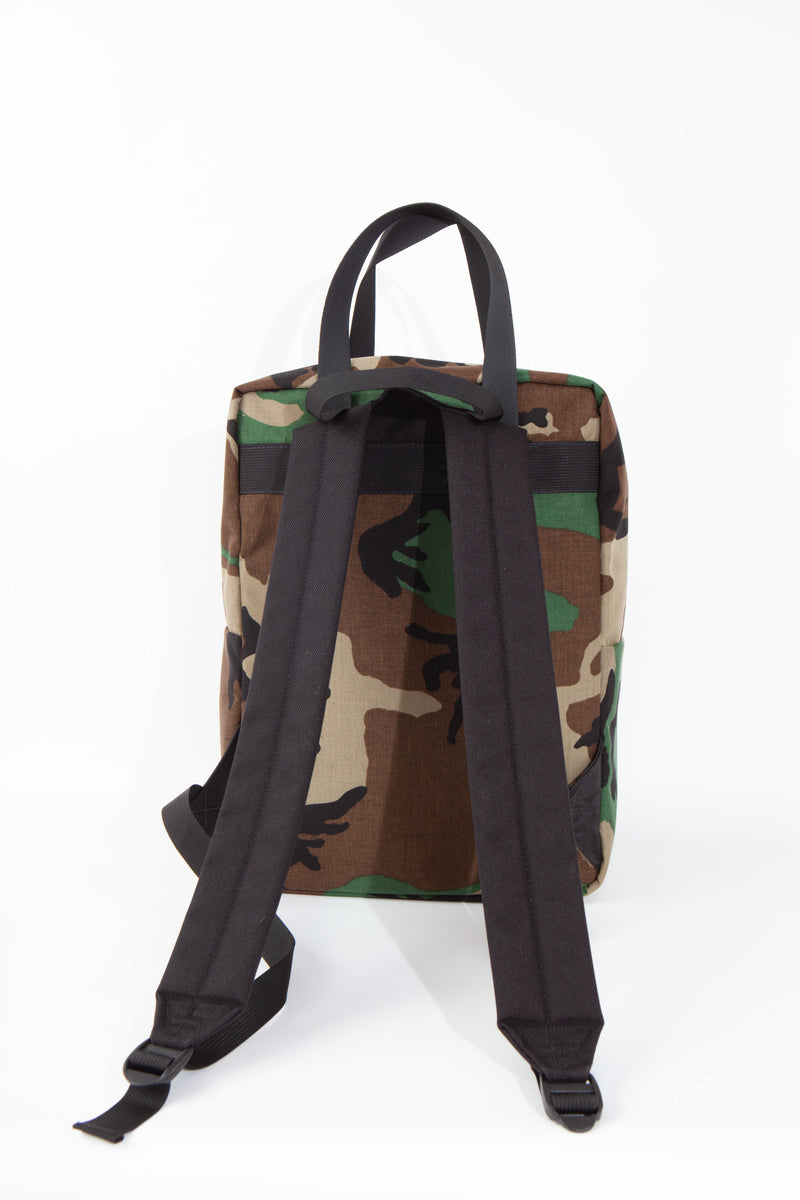 Back view of woodland camouflage backpack with black straps.