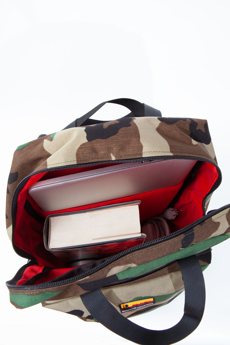 Interior of Havana backpack with red lining and computer and books.