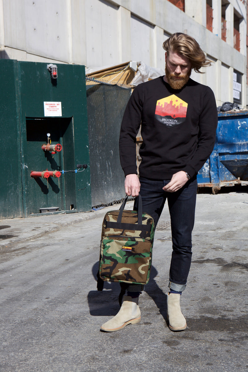Woodland camo backpack being held by model wearing black sweatshirt and black pants against concrete building.