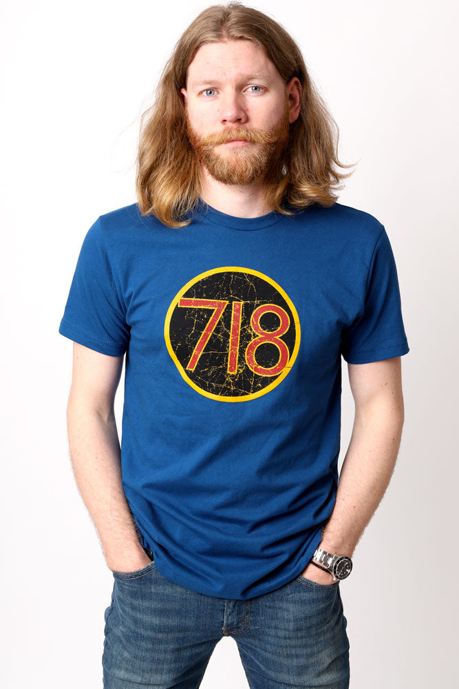man with hands in pockets wears blue graphic t-shirt with 719 in scratchy text