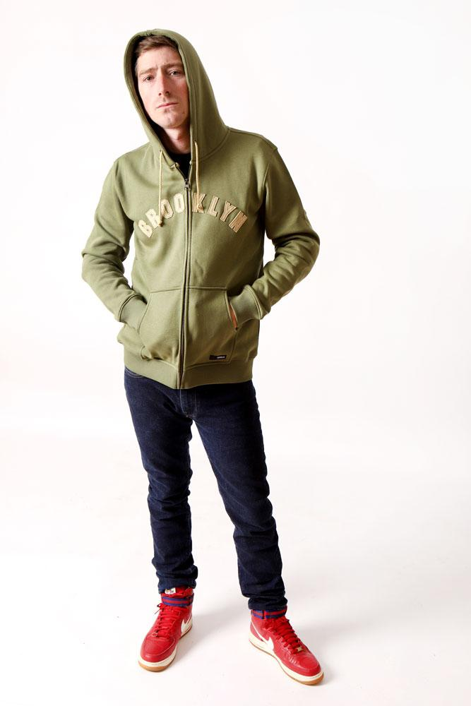 MAN LOOKS AT CAMERA WEARING THE ARCHED BK SWEATSHIRT IN OLIVE GREEN. HANDS IN POCKETS, AND HOOD UP.