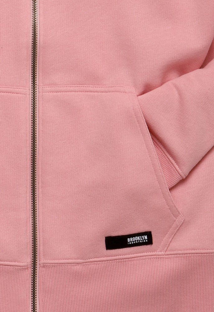 DETAIL OF POCKET ON PINK SWEATSHIRT WITH SLEEVE IN POCKET AND A BLACK BROOKLYN INDUSTRIES PATCH