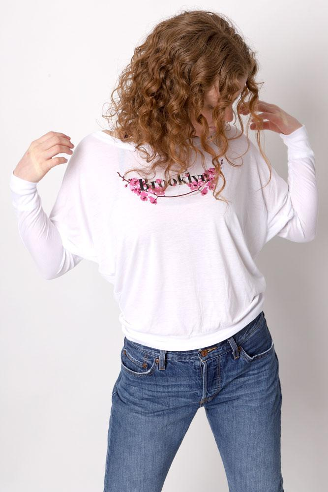 Women's hair covers her face in dolman sleeved long sleeve white shirt with floral brooklyn graphic