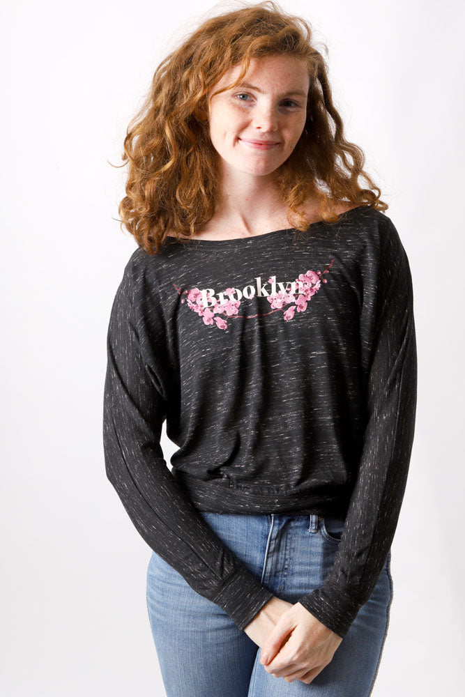 women smiles with red curly hair, wearing a long sleeve scoop neck Brooklyn t-shirt with pink flowers.