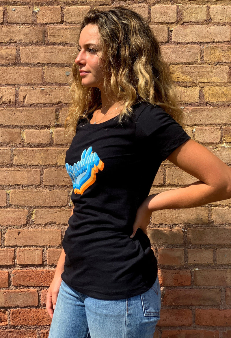 SIDE VIEW OF WOMEN WEARING BLACK BROOKLYN SCRIPT TSHIRT AGAINST A BRICK WALL
