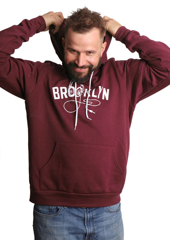 Man pulls on the hood of plum colored unisex hooded sweatshirt