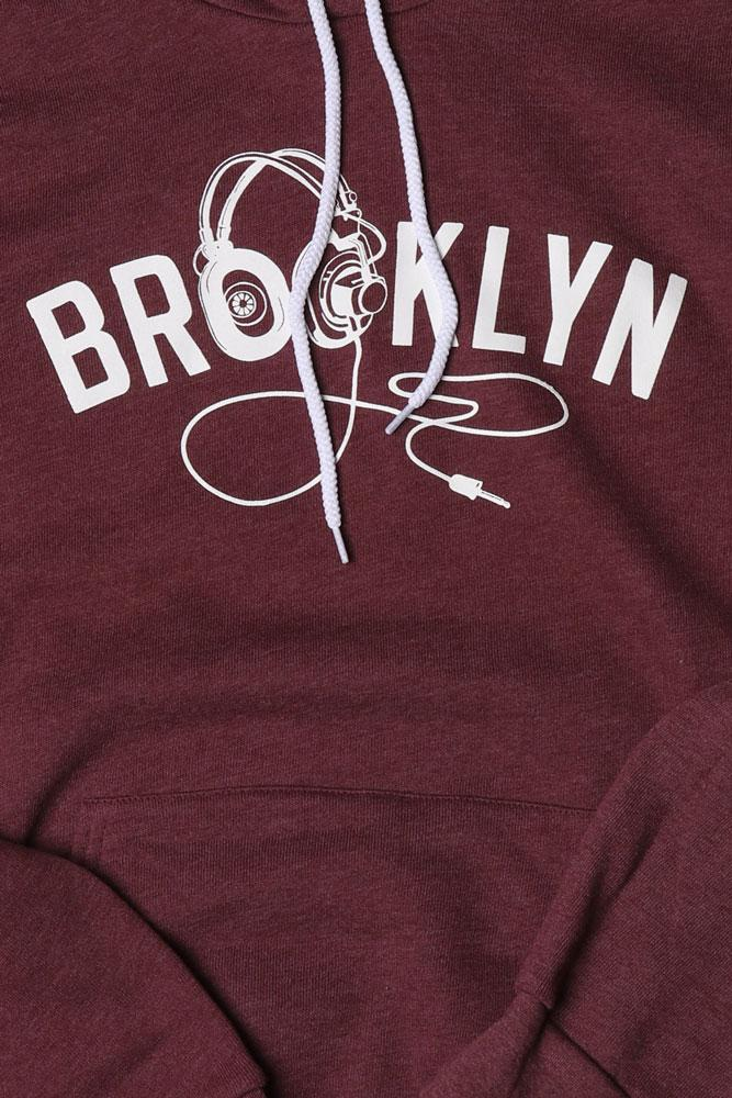 DETAIL OF BROOKLYN INDUSTRIES UNISEX PLUM HOODED SWEATSHIRT WITH HOOD UP, GRAPHIC ON CHEST IS TEXT BROOKLYN WITH HEADPHONES AS THE O'S