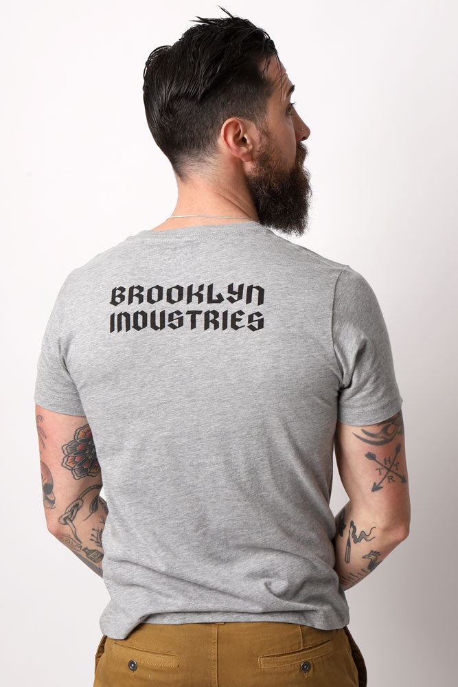 back view of B Bolt t-shirt on man with beard and tattoos - grey shirt with Brooklyn Industries in gothic print across the back