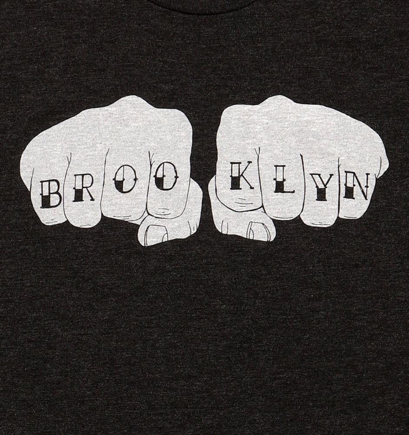 BK KNUCKS T, DARK GREY BODY WITH LIGHT GREY FISTS WITH BROOKLYN TATTOOED ON THE KNUCKLES.