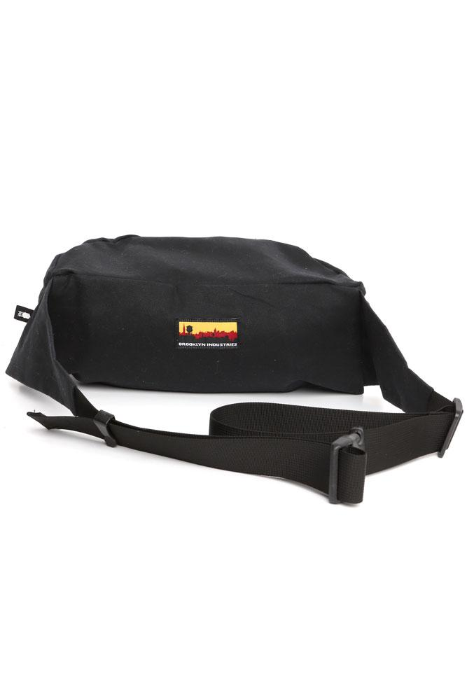 BACK VIEW OF ZEKI WAISTPACK IN BLACK WAXED CANVAS WITH BUCKLE AND SKYLINE LOGO