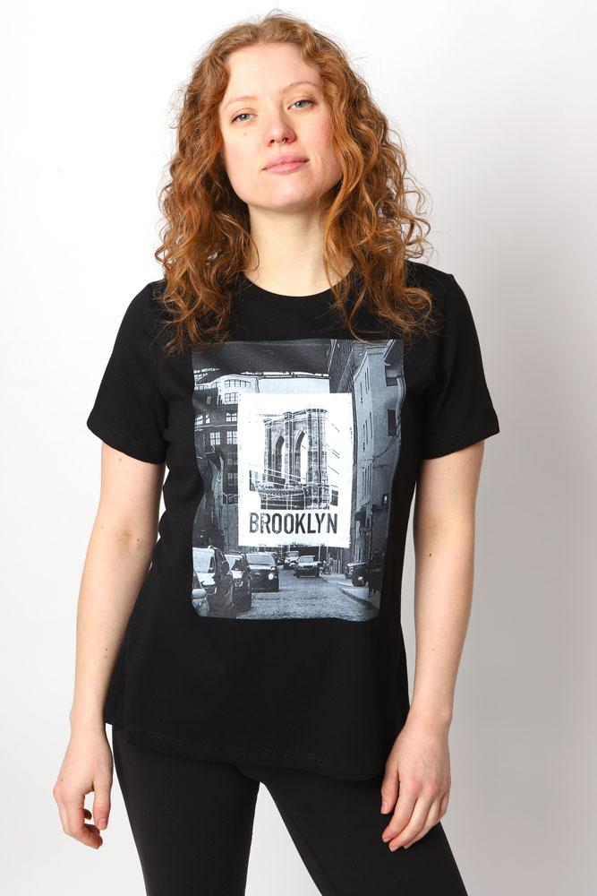 Women wears black graphic t-shirt with street image and bridge images overlayed in a photographic style