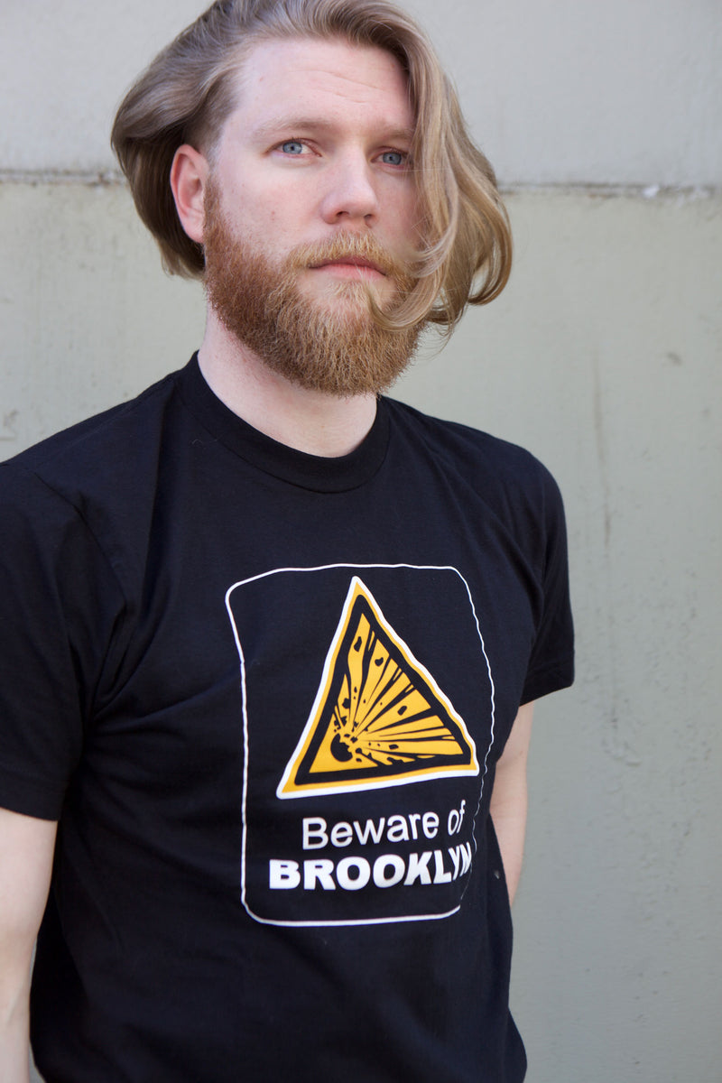 Portrait of man wearing Beware of Brooklyn t-shirt in black