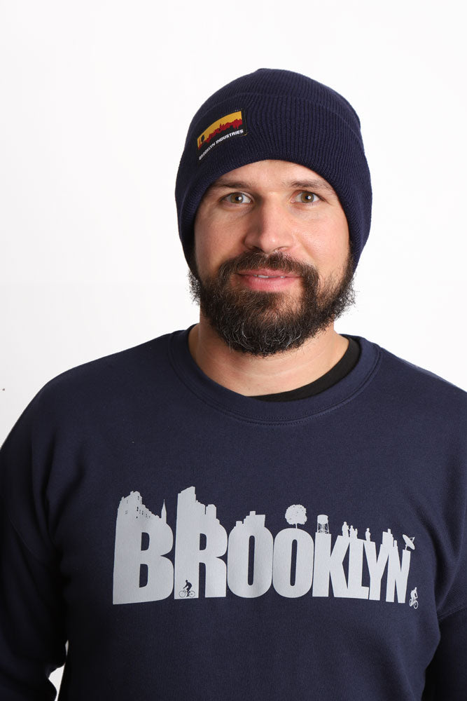 MAN WITH BEARD WEARS BLUE BKI BEANIE AND BLUE BUILDINGS SWEATSHIRT