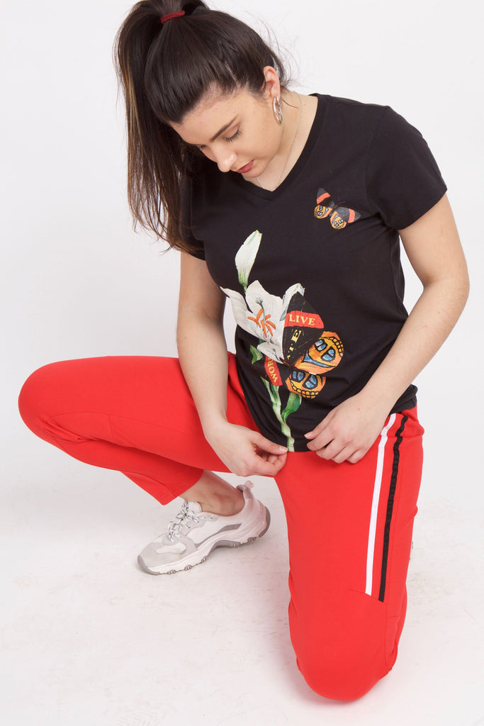 Woman kneeling with black butterfly t-shirt and red sweatpants.  She is looking down at the graphic which has white lillies and butterflies.