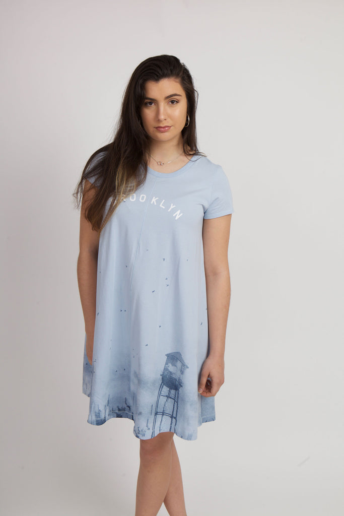 WOMAN WEARING CLOUDY SKYLINE DRESS IN LIGHT BLUE