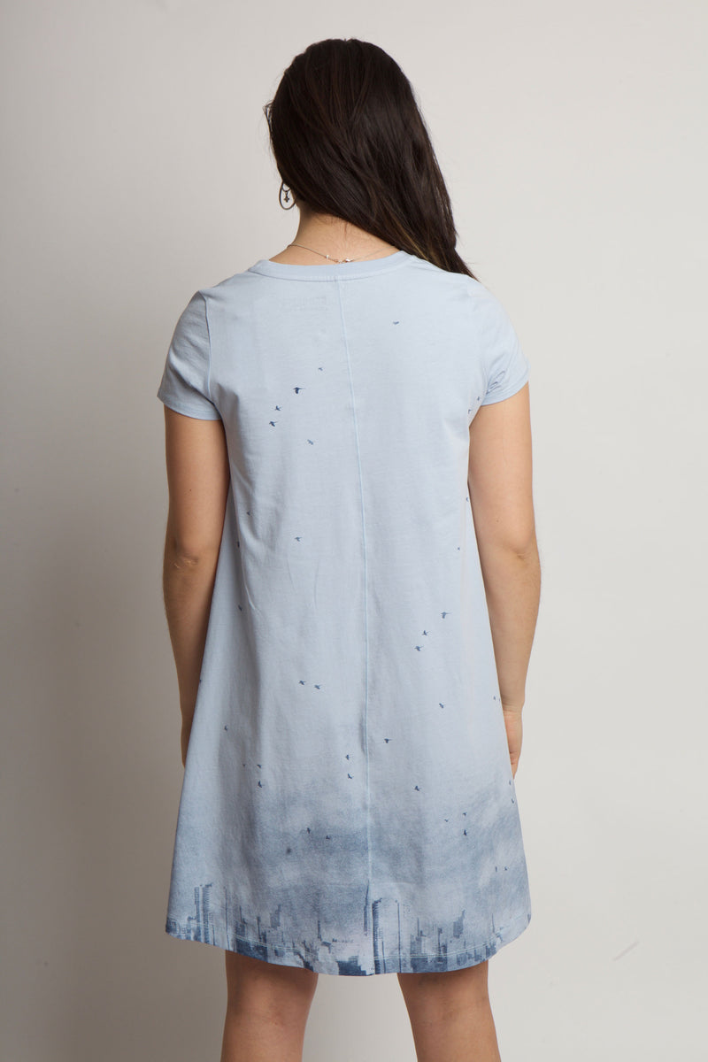 BACK OF WOMENS DRESS WEARING CLOUDY SKYLINE