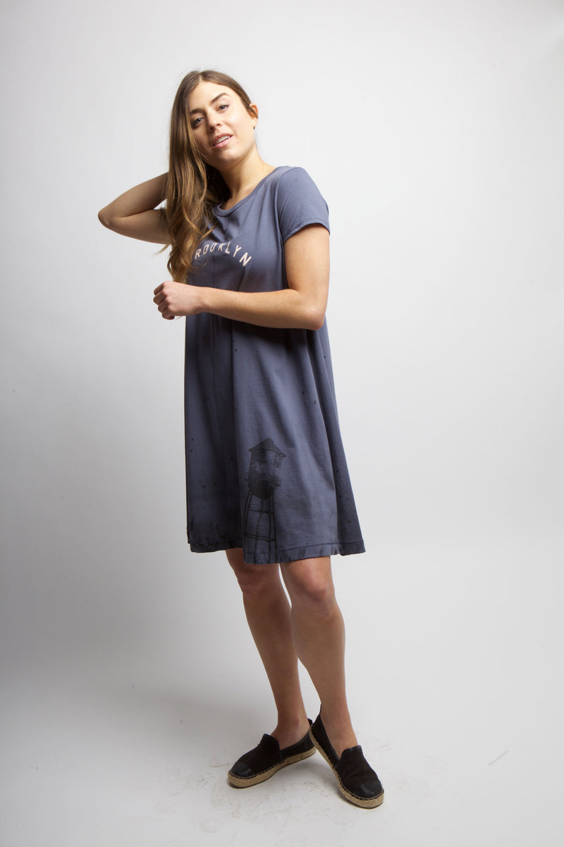 WOMAN IN STUDIO LEANING BACK WEARING CLOUDY SKYLINE DRESS.
