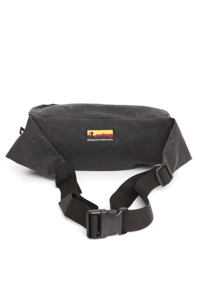 BACK VIEW OF ZEKI WAISTPACK IN COAL WAXED CANVAS WITH SKYLINE LOGO